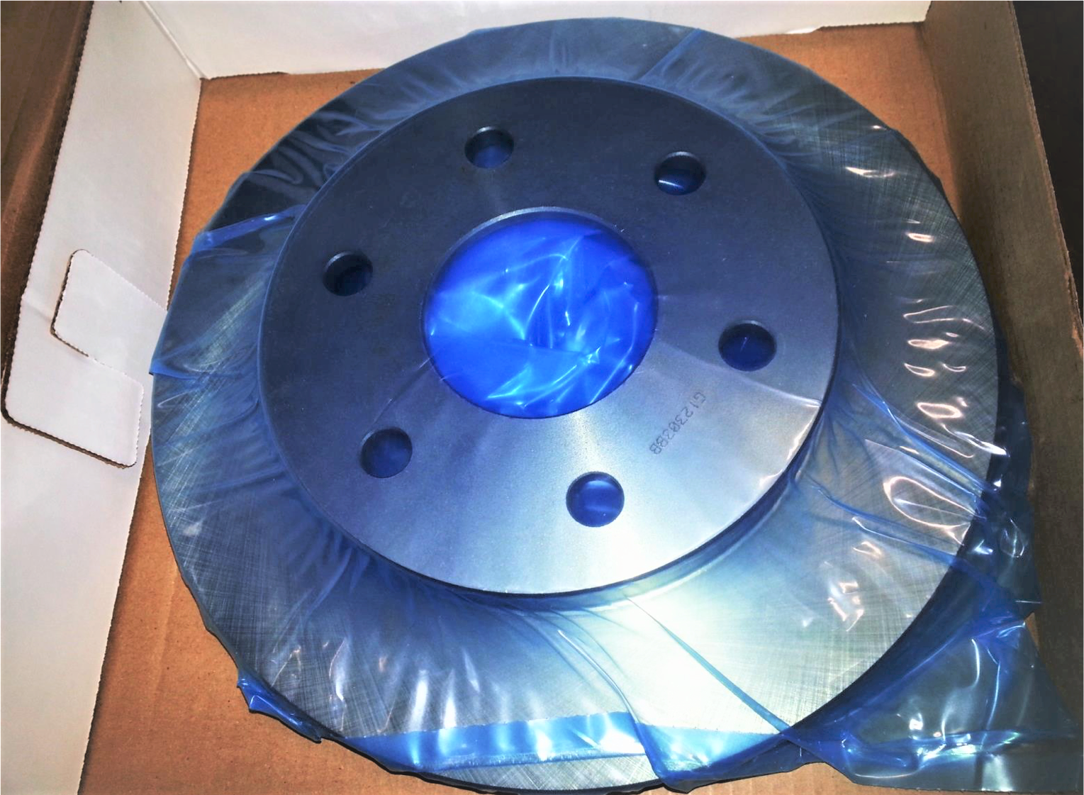 Car part in box wrapped in blue VCI film