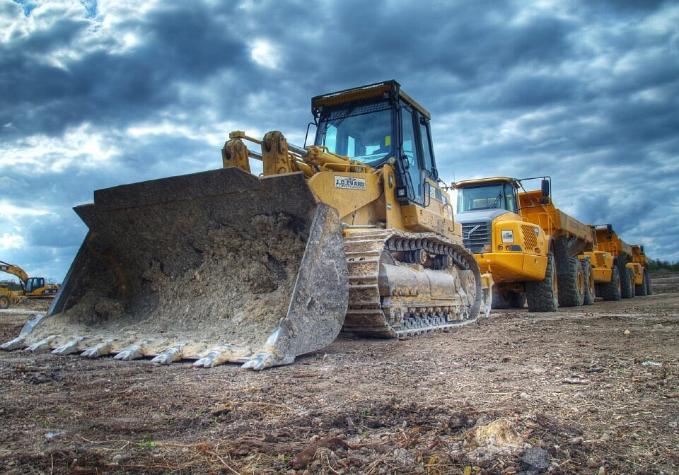 Bulldozer and Heavy Trucks parked in surface mining operation