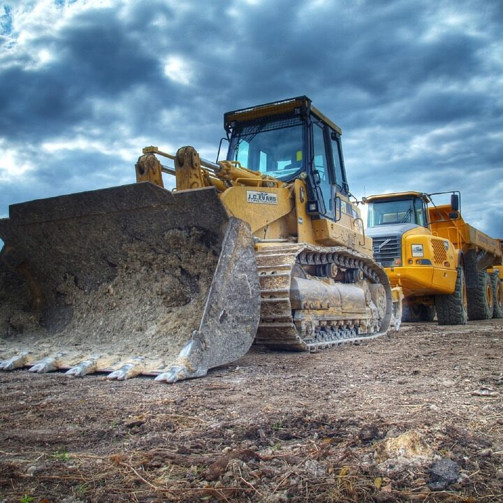 Bulldozer and large trucks parked in surface mining operation with VCI corrosion prevention