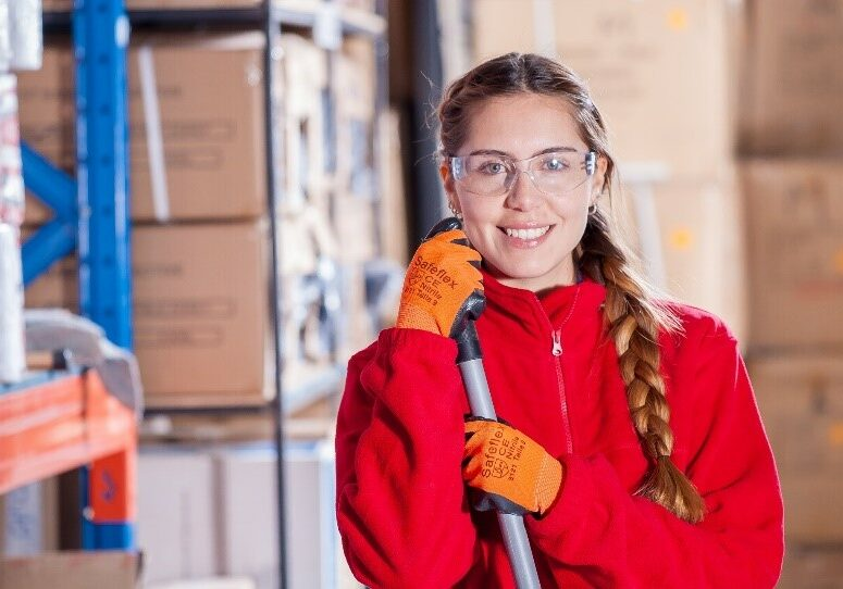 Smiling female Janitor dressed in red overalls