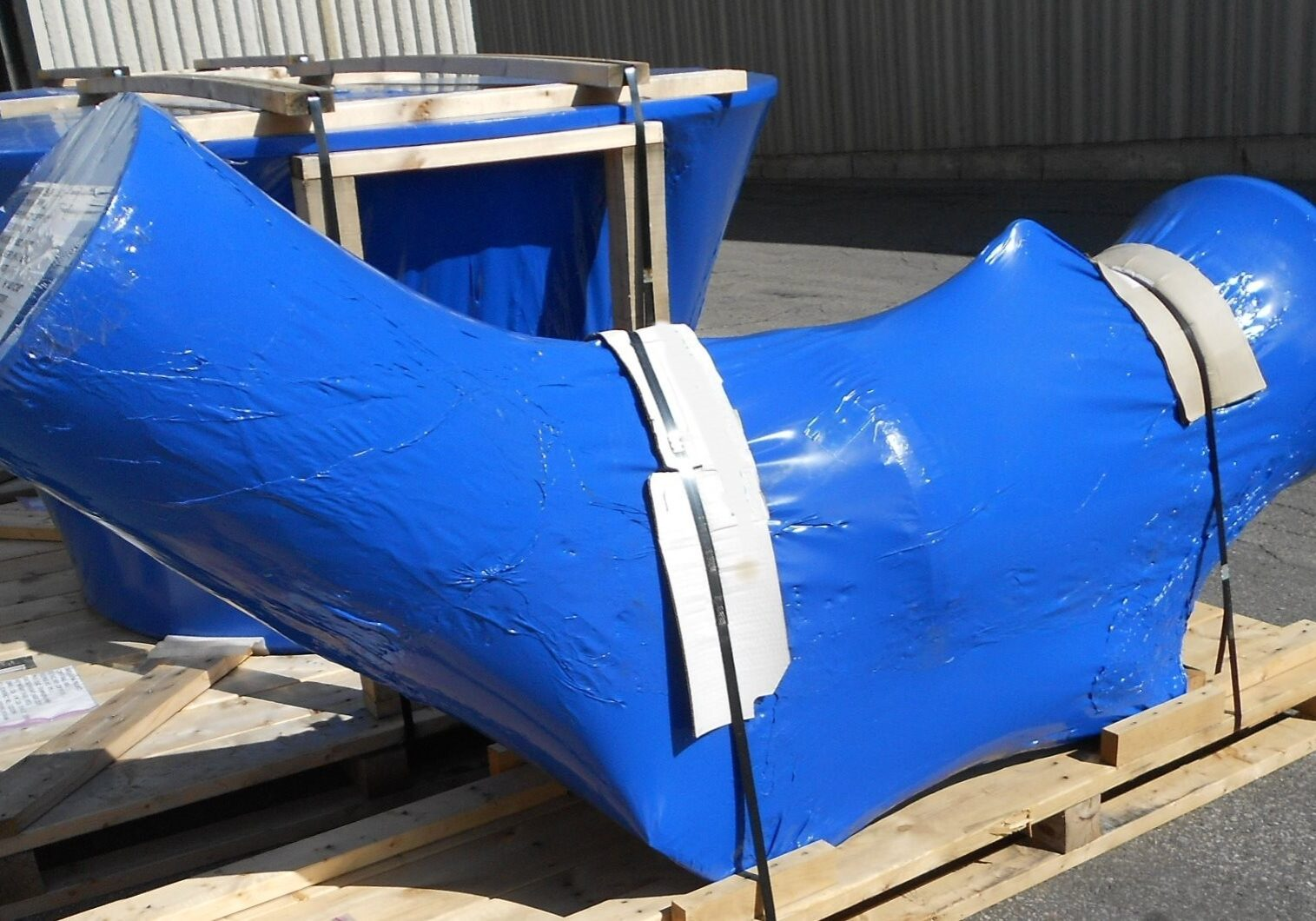 Large outdoor pipe valve wrapped in vci corrosion prevention blue shrink film